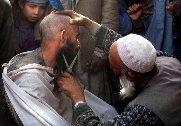 A street hairdresser in Kabul cuts a man's beard.