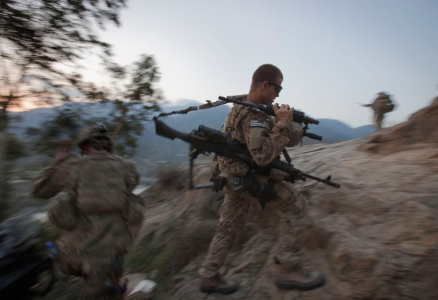 A soldier hikes up to begin an overwatch shift on a hilltop observation post in Afghanistan's mountainous Kunar province.