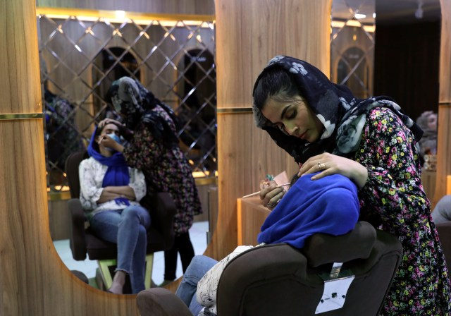 A woman applies makeup on a customer at a beauty Salon in Kabul, Afghanistan.