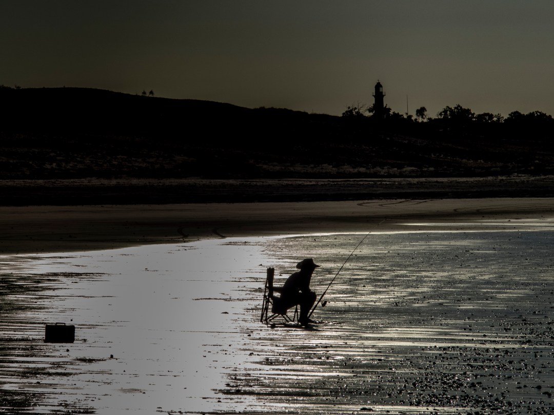 man sits while fishing on beach
