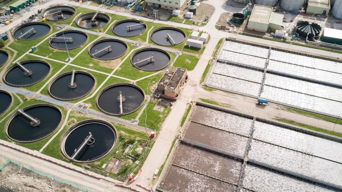 An aerial view of purification tanks and ponds at a waste water treatment works.