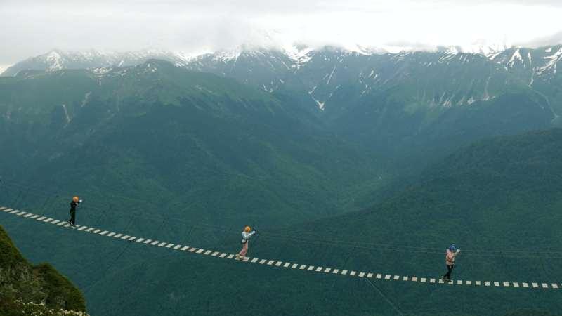Three people cross a rope bridge against mountain backdrop.