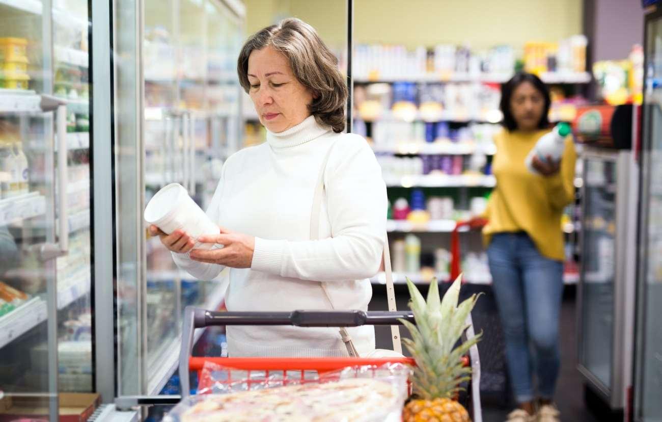 La donna in supermercato esamina la confezione di un contenitore di yogurt.