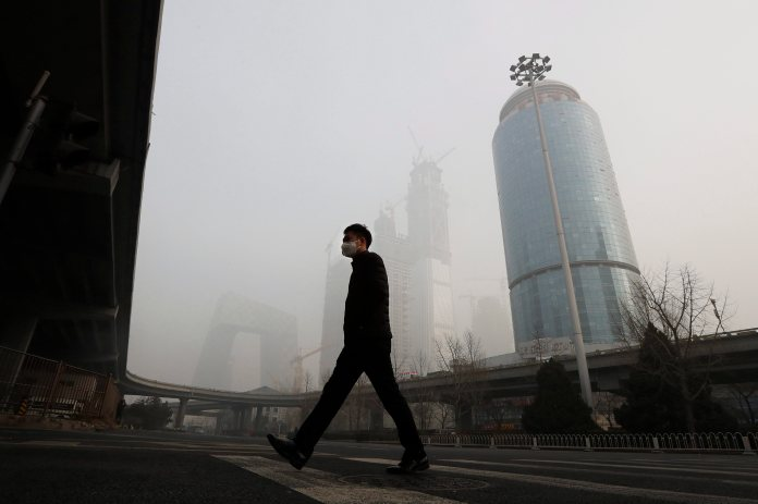 A man wearing a mask walks in smog.