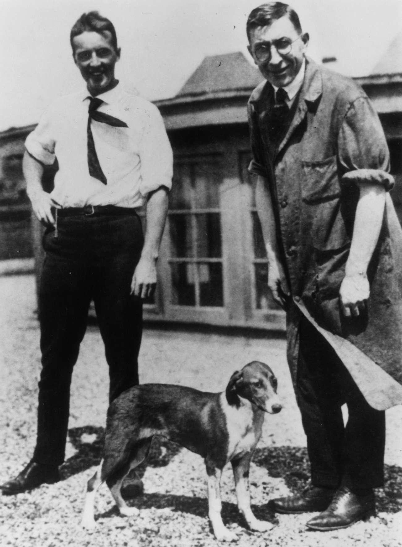 due uomini vestiti all'inizio del XX secolo in piedi con un cane tra di loro