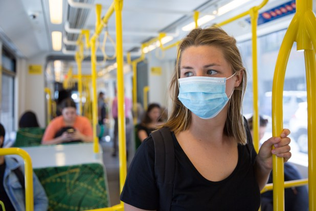 A woman wearing a face mask on a bus