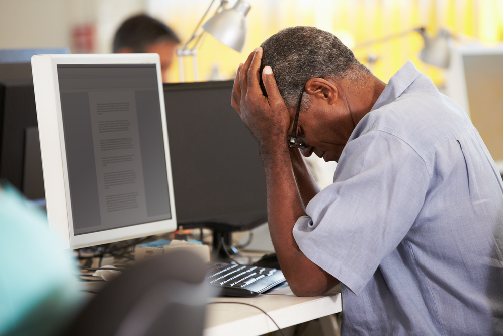 Older man holds head in front of a computer.