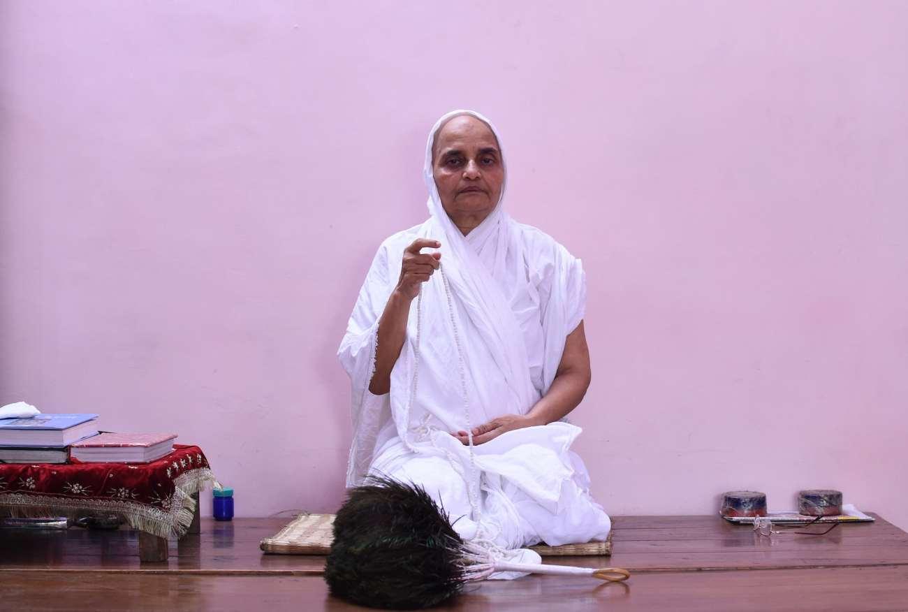 Una suora giainista prega in una stanza del tempio giainista nei vecchi quartieri di Nuova Delhi.