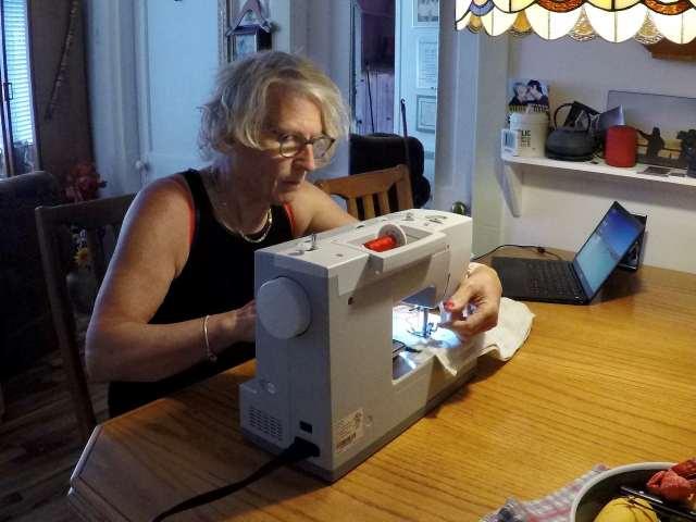Une dame est installée devant une machine à coudre