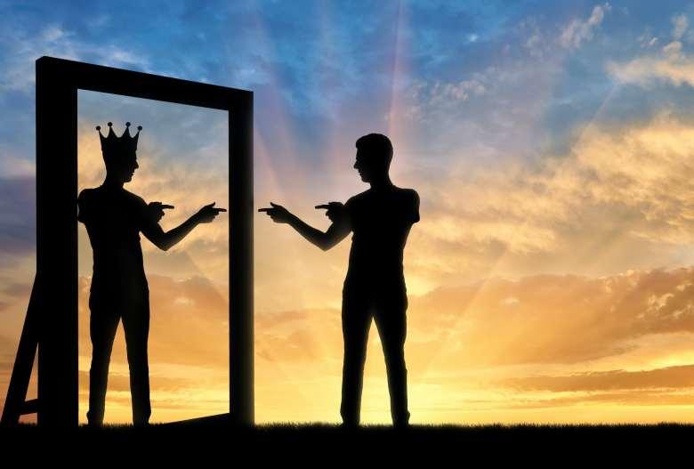 Silueta de un hombre señalándose a sí mismo en el espejo, su reflejo lleva una corona.