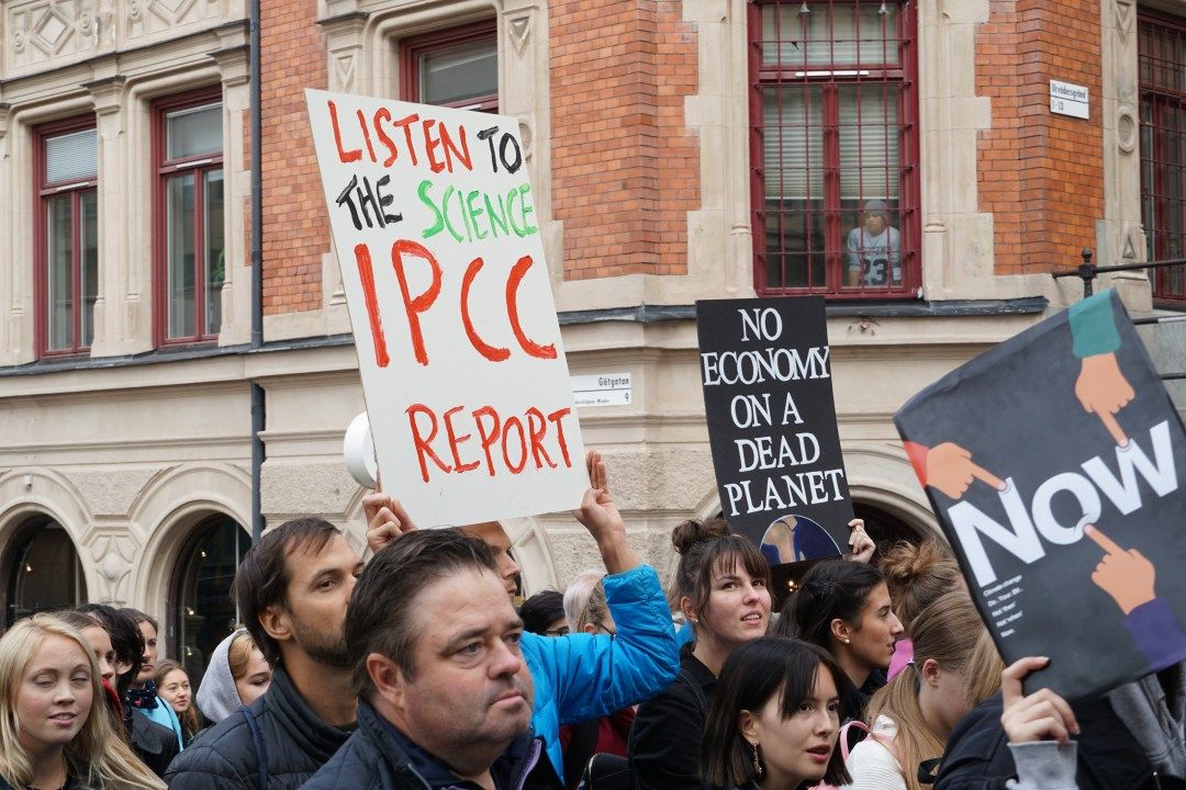A protester holding a sign that says 'listen to the science, IPCC report'.