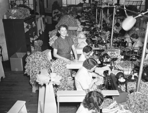 A large room is full of women sitting at tables and using sewing machines to make garments, while a woman is standing, in 1937