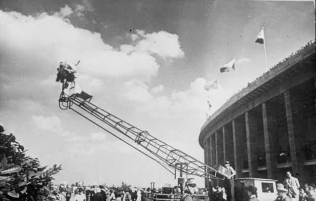 A black and white image of a cameraman on a crane above a crowd