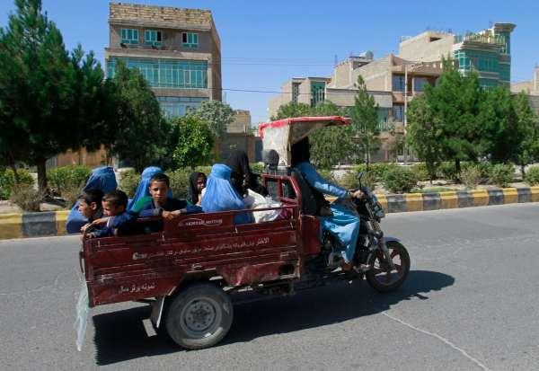Mujeres y niños afganos viajan en un carro de motocicleta