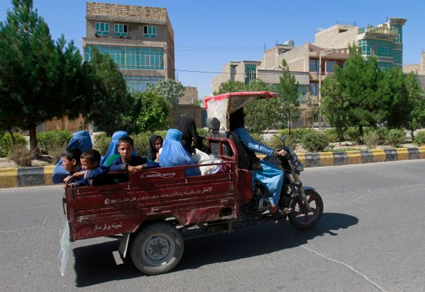 Afghan women and children travel in a motorcycle cart
