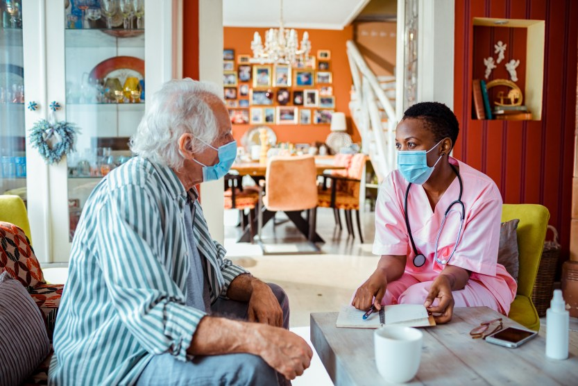 Health care worker talking to an older patient.