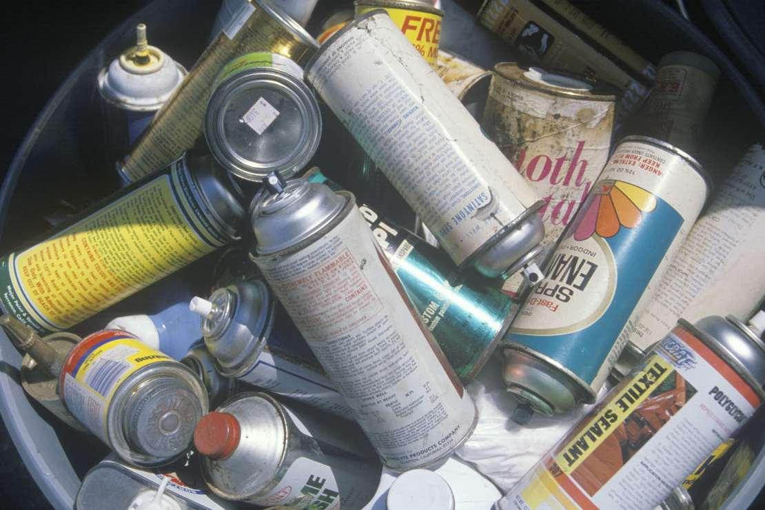 A bin full of discarded aerosol cans.