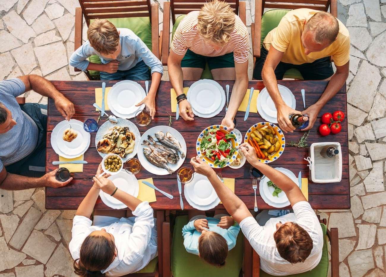 Una famiglia seduta a tavola a mangiare.