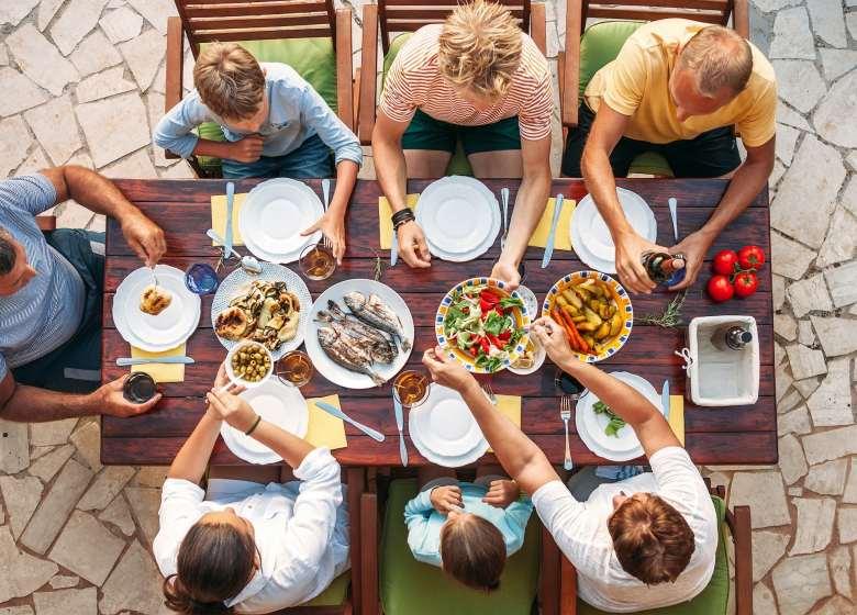 Una familia sentada alrededor de una mesa comiendo.