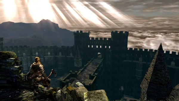 A knight in armour faces a sun-streaked sky and wall of ruins.