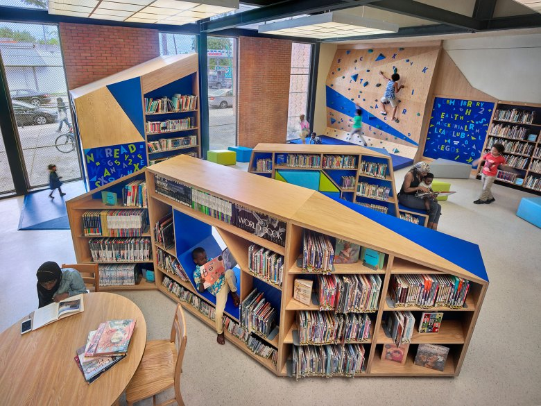 Children read books and play on climbing wall in library