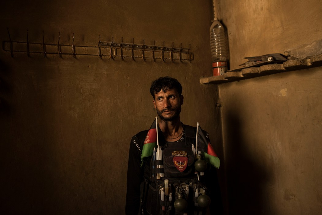 A soldier with the Afghan National Army stands in a room at an a building previously used as of a jail by ISIS-K.