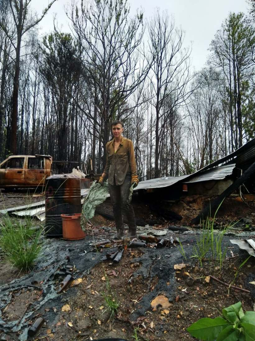 A person stands in a burnt-out home