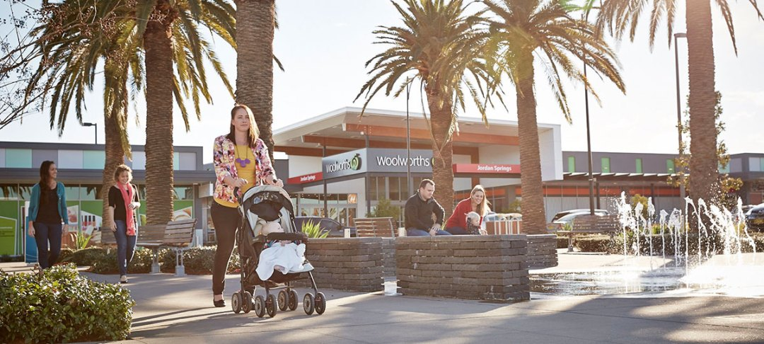 woman pushes pram in front of supermarket