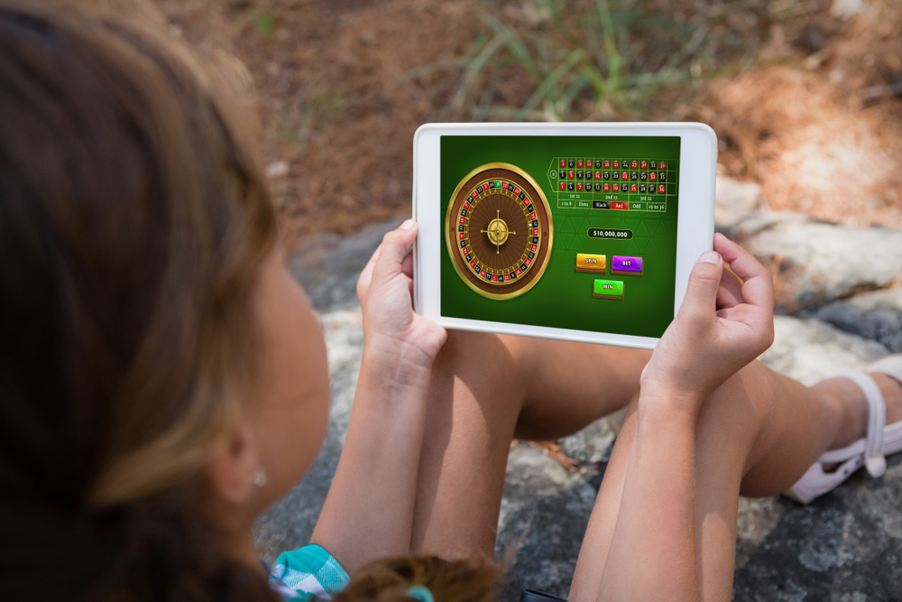 A woman holds a tablet with gambling software on it