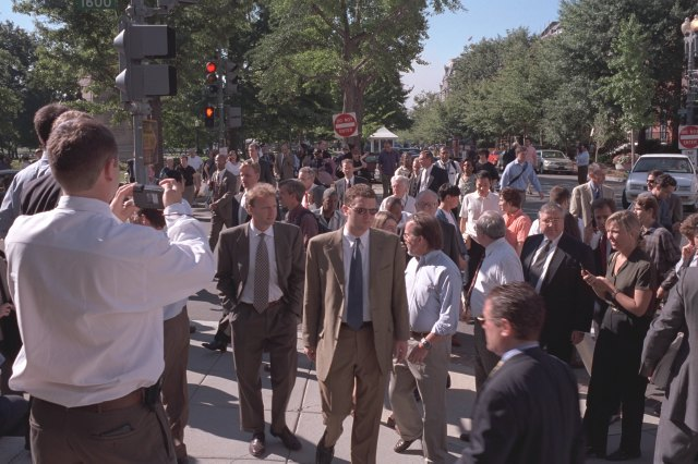 A crowd of people outside of the White House, on a street.