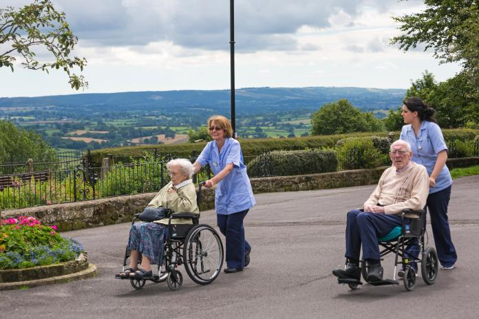 Two elderly people in wheelchairs being pushed out by carers