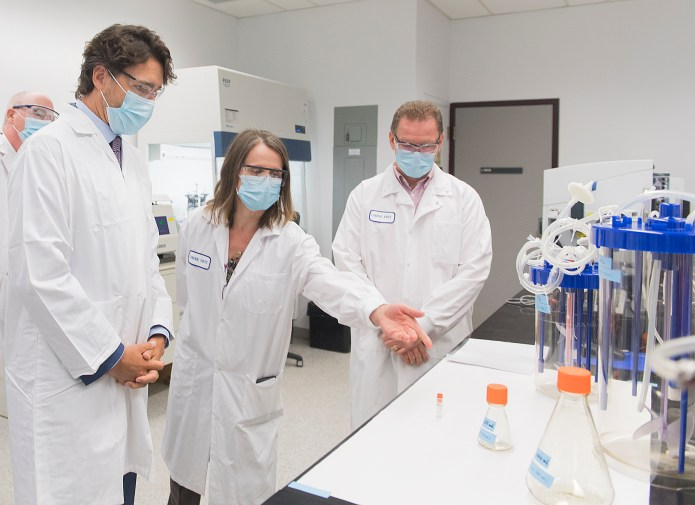 Justin Trudeau surrounded by scientists in a lab