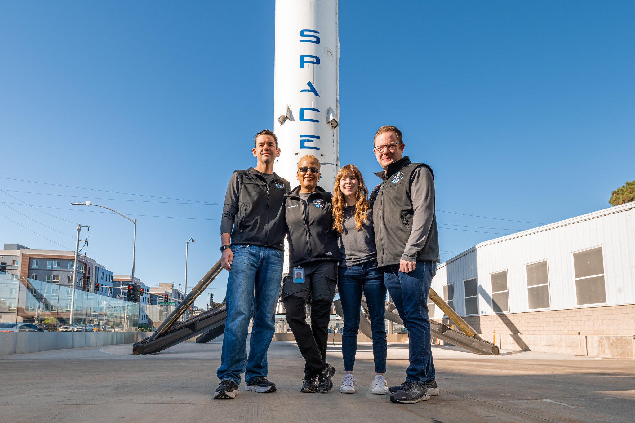 Four people standing in front of a rocket.