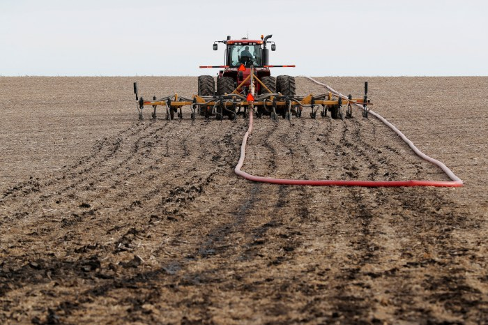A tractor spreads manure on a dirt field.