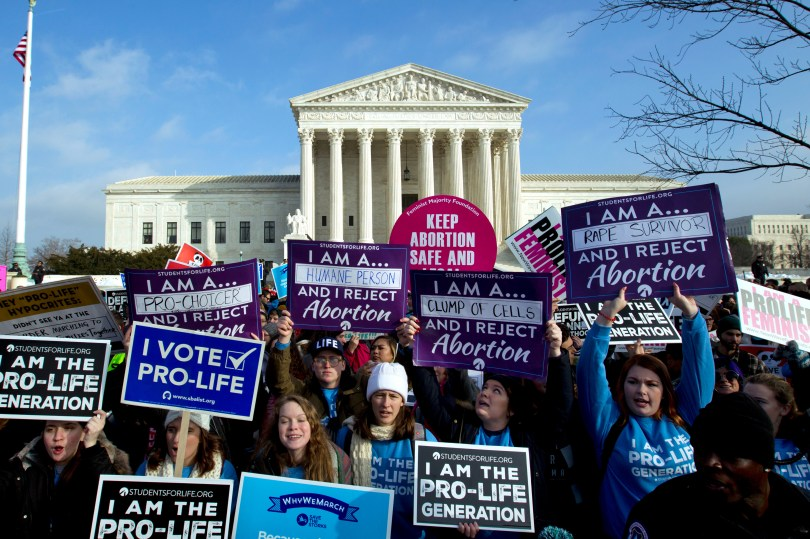 Anti-abortion activists holding signs in front of the Supreme Court.