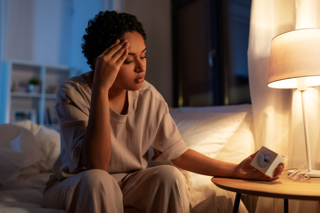 A woman sits on the edge of her bed, looking at her bedside clock.