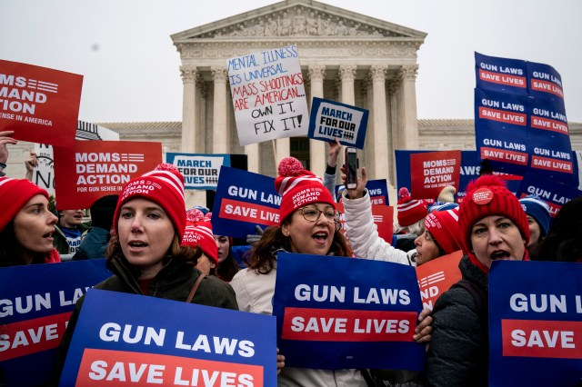 A crowd of people hold signs about gun laws in front of the U.S. Supreme Court building