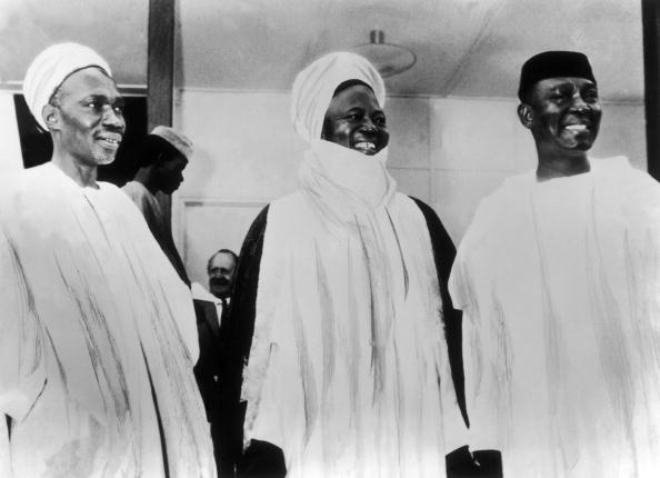 Three men standing and holding hands. The first two from the left are wearing head turbans.