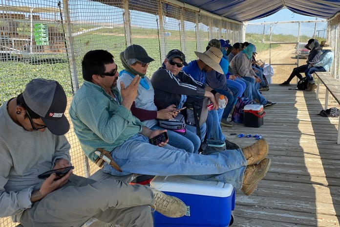 About a dozen farm workers in long sleeves, jeans, hats and boots sat in the shade of a covered open truck bed.