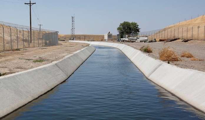 A concrete canal running through dry terrain.