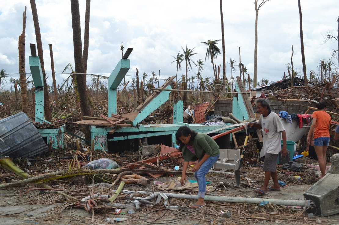 People in front of house destroyed by a typhoon.