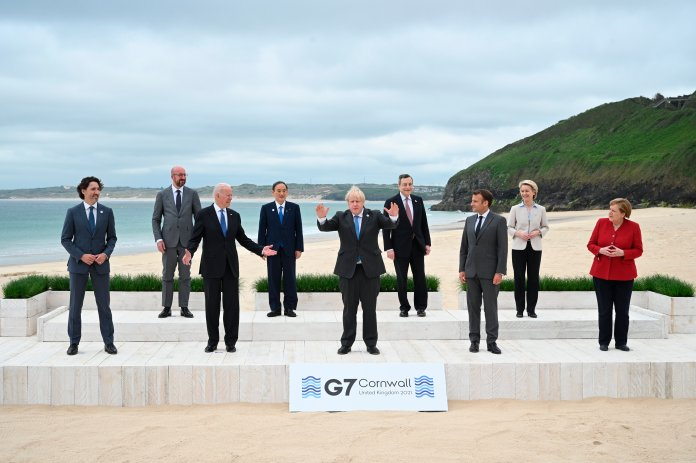 Boris Johnson stands in front of other G-7 leaders on a beach.