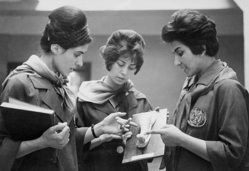 Two Afghan female medicine students examine a plaster model showing a part of a human body with the instructor.