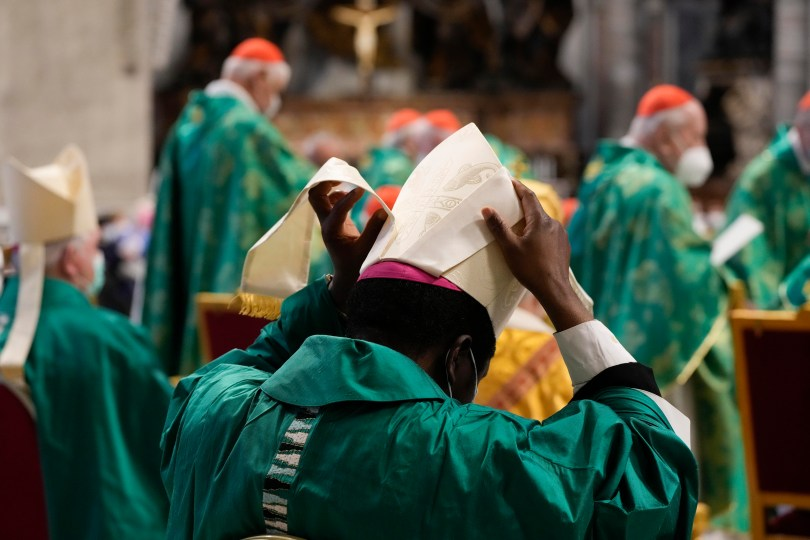 A Bishop in green robes adjusts his hat at a mass in St. Peter's Basilica in the Vatican.