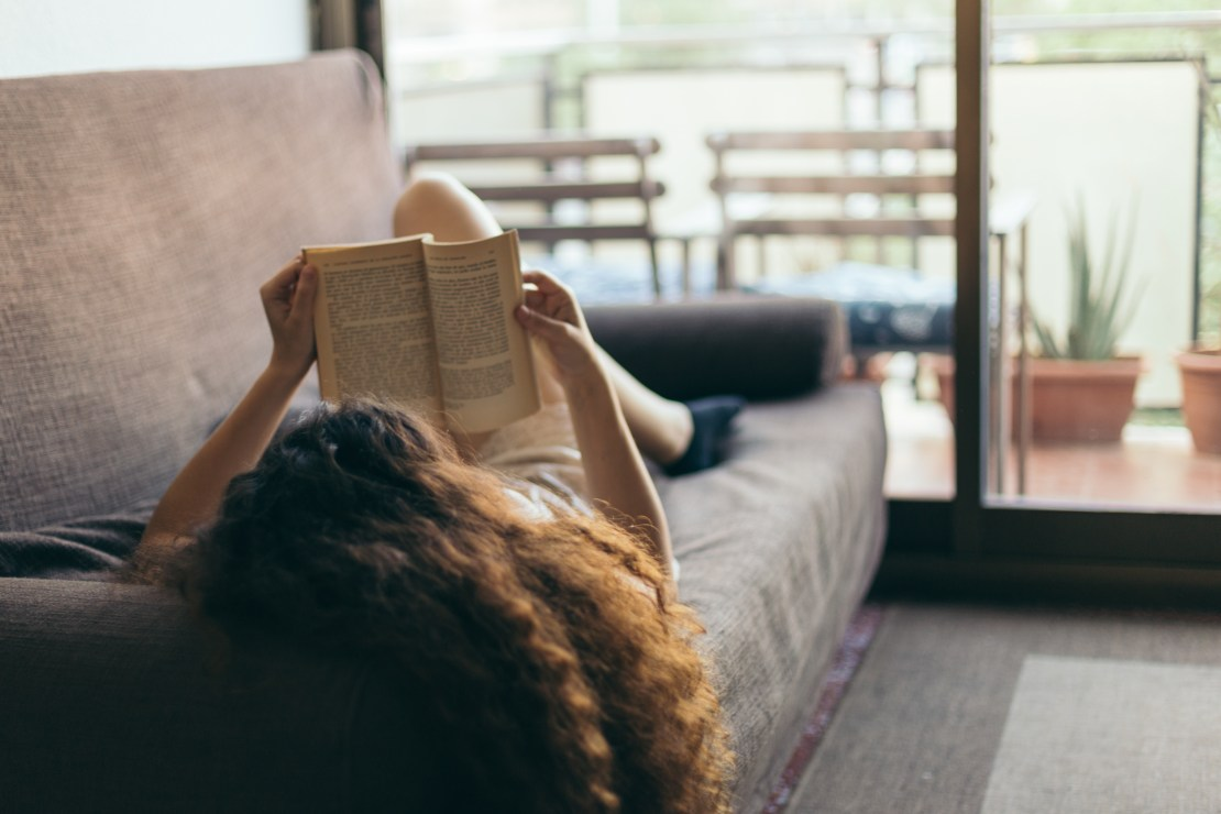 A woman lying on a sofa reading a book
