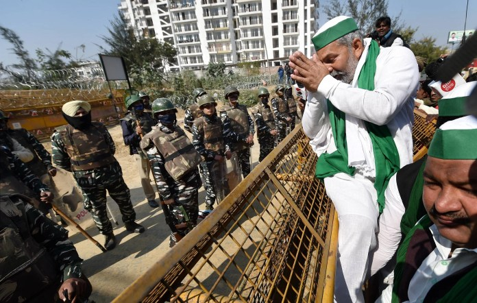 Security personnel stand near barricades as BKU spokesperson Rakesh Tikait gestures during the chakka jam by farmers at the Delhi-Ghazipur border
