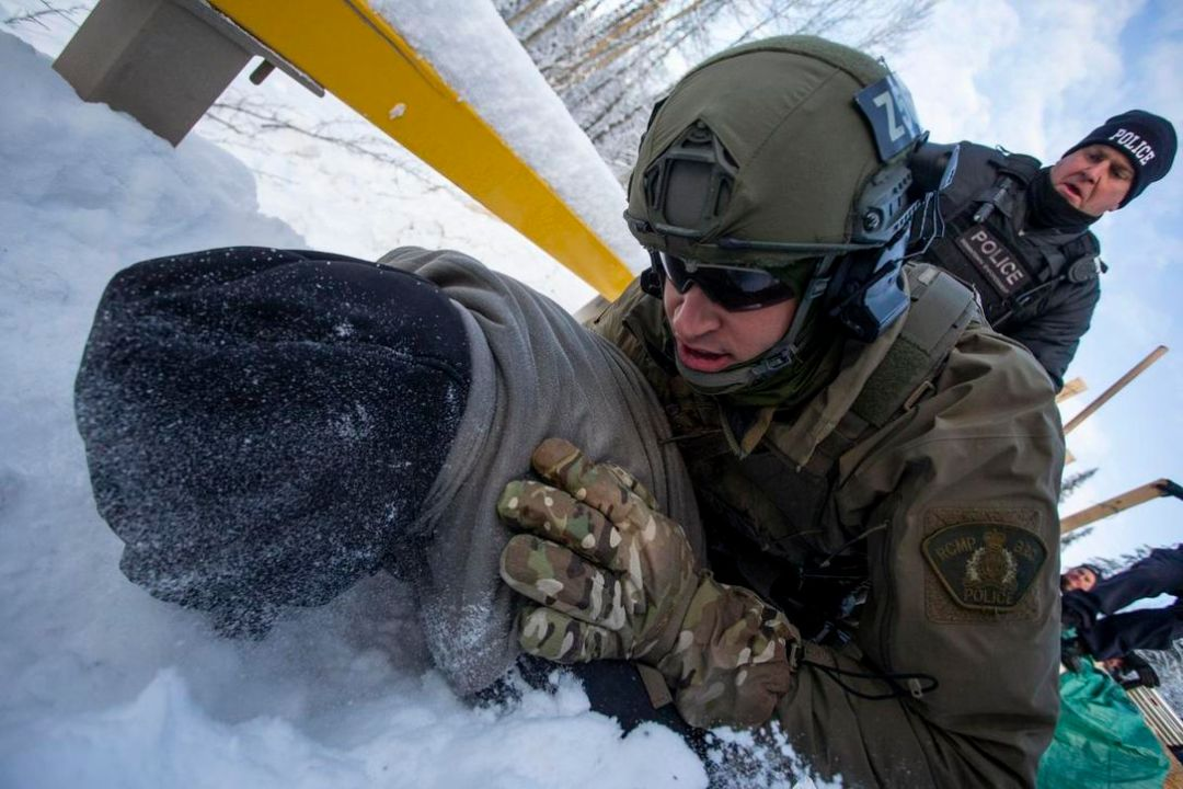A land defender is tackled to the ground by an RCMP officer in tactical gear after police breached the Gitimt'en checkpoint barricade on Monday, January 7, 2019. Fourteen people were arrested at the barricade.