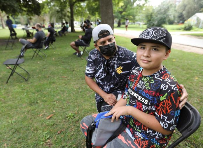 12-year-old Michael Castro got his first vaccine at Trinity Bellwoods so that he could attend his boxing class.  Michael was taken to the clinic by his father, Eric.
