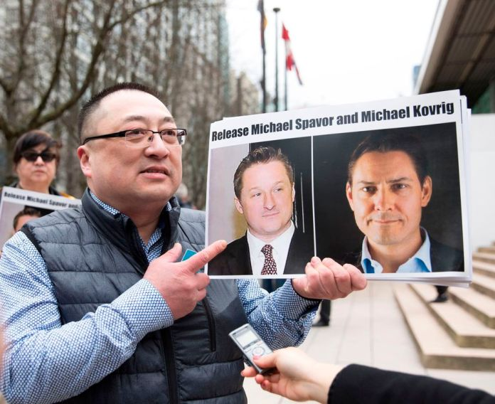 Louis Huang of Vancouver Freedom and Democracy for China holds photos of Canadians Michael Spavor and Michael Kovrig, who are detained by China, in Vancouver, Canada, on May 16, 2019.