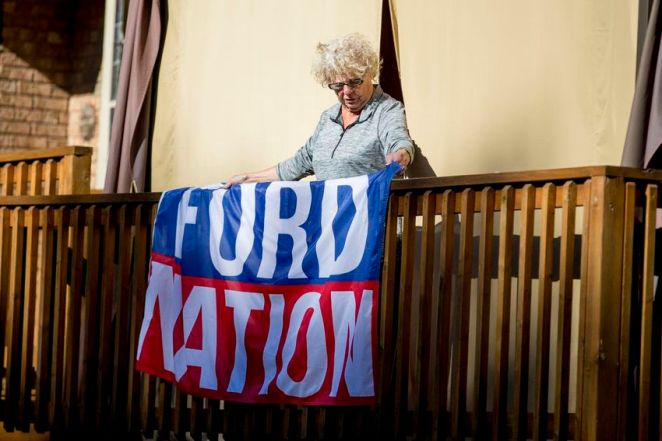 """Diane Ford hangs a banner ahead of the announcement of Doug Ford's book """"Ford Nation: Two Brothers, One Vision"""" in September 2016."""